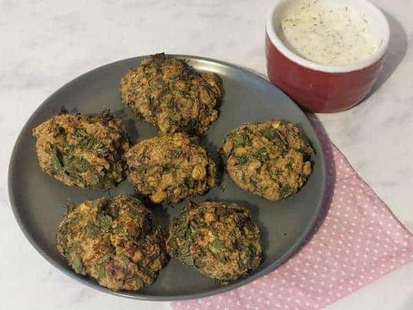 falafel on a grey plate with red ramekin of white coloured dip