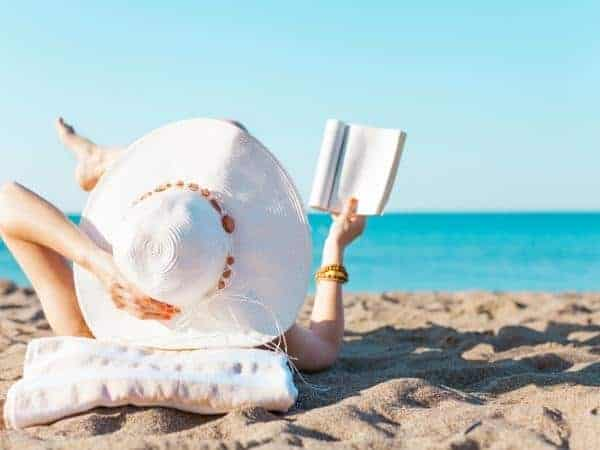 lady reading on the beach in the sun wearing wide brimmed hat