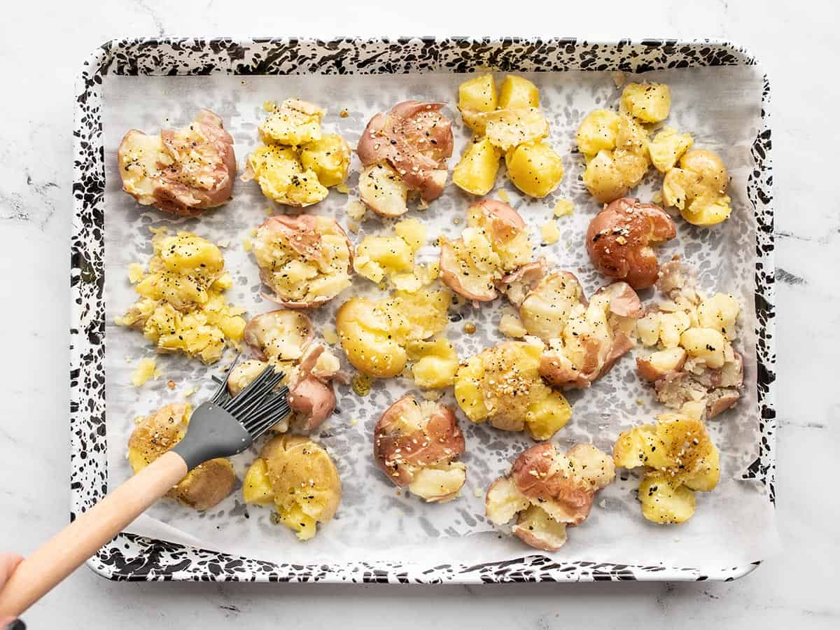 Seasoned oil being brushed over the smashed potatoes