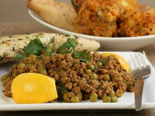 Square white plate of keema curry with peas showing and lemon wedge, naan bread and a fork